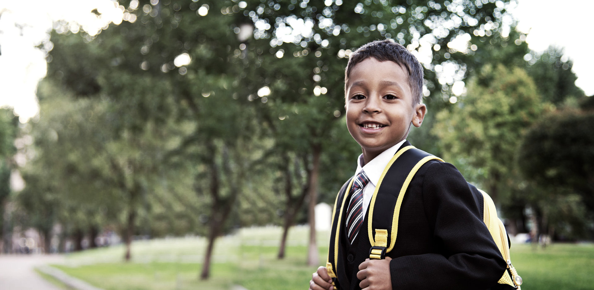 smiling little boy wearing a formal attire with bag