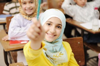 little girl raise her pen while smiling